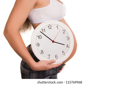 The pregnant young woman holds white clocks