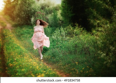 Pregnant young woman in light pink dress running in the woods in the summer