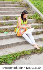 pregnant young woman sits on a old stairs and paints aquarelle in a park