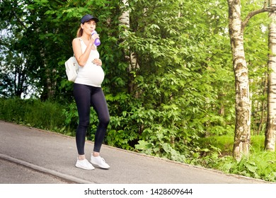 A pregnant young woman in a tracksuit and a baseball cap walks in the Park among the greenery and trees during sports training.
