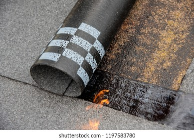 Preheating the edges of the roofing material. Repair work on the roof. Heating of the roofing material.  Installation by heating and melting of bitumen rolls. waterproofing
