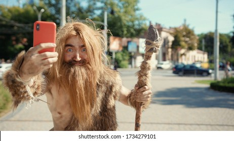 Prehistoric tribesman of neanderthals noticing somebody hurrying taking photographs like paparazzi on future smartphone in modern civilization city.