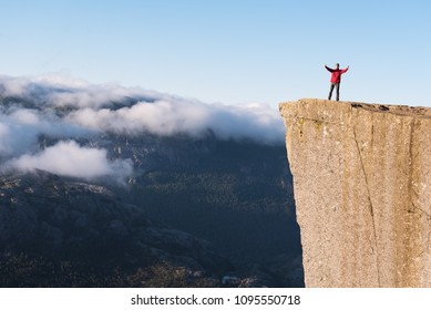 Preikestolen - amazing rock in Norway. Guy on a cliff above the clouds. Pulpit Rock, the most famous tourist attraction in Ryfylke, towers over the Lysefjord