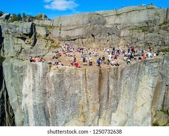 PREIKESTOLEN, NORWAY - JULY 23, 2017: Tourists at Preikestolen or Prekestolen or Pulpit Rock, famous tourist attraction near Stavanger, Norway. Preikestolen is a cliff, rises above Lysefjord.