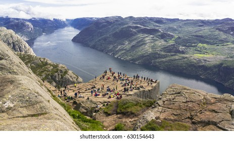 Preikestolen, Norway - July 27, 2016: The most famous viewing point of Norway 600m above sea level. By the Lysefiord. Cloudy day tourists have amazing view of Lysefjord.