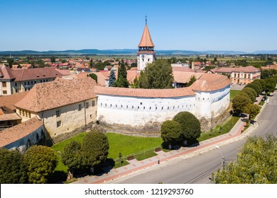 Prejmer Fortified Church, Brasov County, Transylvania, Romania. Aerial view. Medieval fortress with a church, clock tower, high spire, thick walls, red tiled roofs, surrounded by a town, Transilvania.