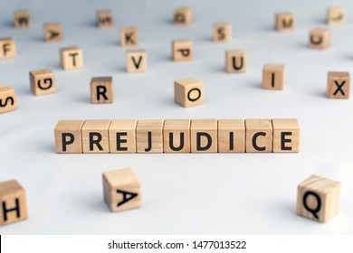 prejudice - word from wooden blocks with letters,  personal opinions prejudice bias concept, random letters around, white  background