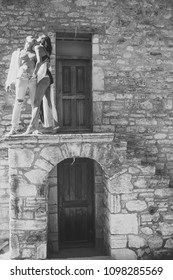 Prelude - couple in love. Woman in black lingerie, man with nude torso stands outdoor. Couple enjoys nudity. Sexy couple undressing under sunlight with ancient rocky wall and old door on background
