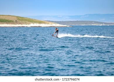 Premantura, Croatia,August 6, 2019, man riding on water board with engine.