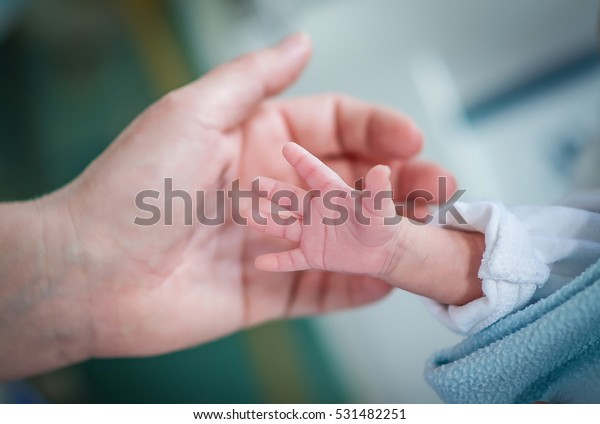 Premature baby in an incubator chamber reaching for his mother's hand