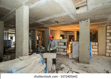 Premises before leveling, finishing, painting, plastering. Сonstruction monolithic house. Layout of building materials bricks foam blocks. Drywall installation work in progress by workers. Moscow 2019