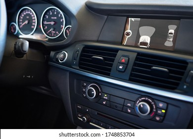 Premium car interior backup parking assistant system with sensors on screen with out of focus dashboard and steering wheel. Driver assistance system for parking. Help assist options inside luxury car.