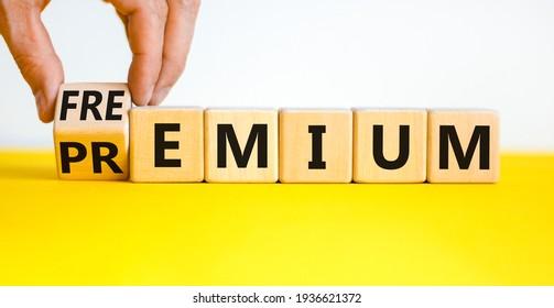 Premium or freemium symbol. Businessman turns the wooden cube, changes the word 'premium' to 'freemium'. Beautiful yellow table, white background. Business, premium or freemium concept. Copy space.