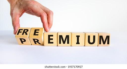 Premium or freemium symbol. Businessman turns wooden cubes and changes the word 'premium' to 'freemium'. Beautiful white background. Business, premium or freemium concept. Copy space.