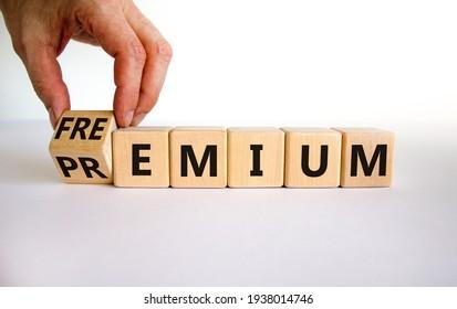 Premium or freemium symbol. Businessman turns the wooden cube and changes the word 'premium' to 'freemium'. Beautiful white background. Business, premium or freemium concept. Copy space.