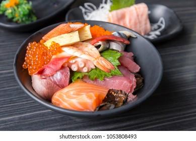 Premium fresh raw seafood mixed rice bowl (Kaisen-don/ Japanese tasty food), Japanese Rice with sashimi of tuna, Maguro, Otoro, salmon, squid and ikura (Salmon eggs) on wood background