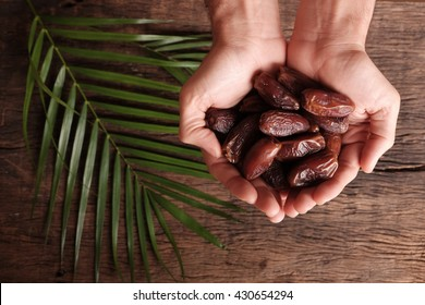 Premium grade dates in palms with space for taxt isolated on wooden background