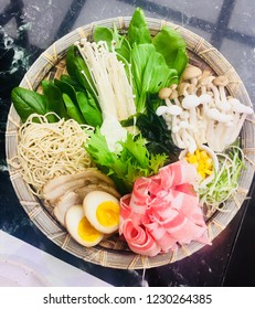Premium Japanese dining shabu and sukiyaki in hot pot at japanese restaurant, hot pot with ingredients slice beef egg vegetable wagyu beef sliced on plate for Shabu cooking in hot boil soup.