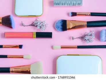 premium makeup brushes, eyeshadow palette, blush and listick on a colored pink background, creative cosmetics flat lay