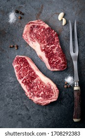 Premium quality marbled Japanese Wagyu beef on a dark stone background, fresh New York steak