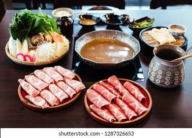 Premium Rare Slices Kurobuta (Black Pig) pork with high-marbled texture on circle wooden plates served with vegetable set for Sukiyaki and Shabu.