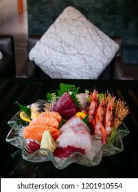 Premium sashimi on ice, Tai fish Ebi sashimi, Maguro sashimi, salmon sashimi - Dark background warm tone image