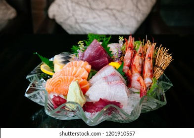 Premium sashimi on ice, Tai fish Ebi sashimi, Maguro sashimi, salmon sashimi - Dark background warm tone image