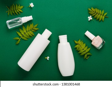 Premium skin care cosmetics, perfume on green rustic background  with green leaves. White bottles of woman cosmetics. Natural organic cosmetics. Shampoo, tonic, cream, hairbrush, nail polish. Top view