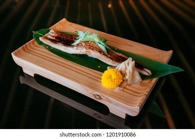 Premium Unagi sushi on wood plate, whole large piece Japanese Unagi eel sushi, Dark background warm tone image