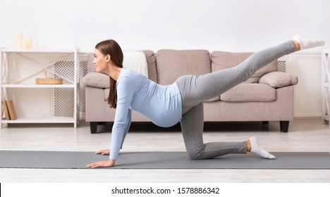 Prenatal Exercises For Healthy Delivery. Pregnant woman doing back leg raises or donkey kick on yoga mat. Copy space