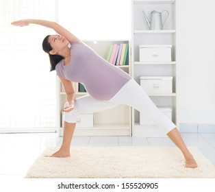 Prenatal health concept. Full length healthy 8 months pregnant calm Asian woman meditating or doing yoga exercise at home. Relaxation yoga side stretching pose.