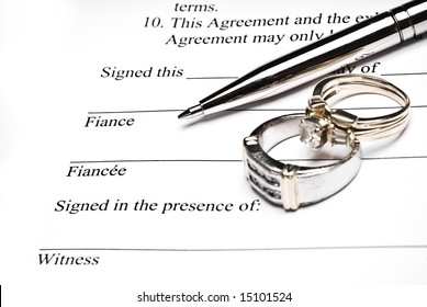 Prenuptial agreement with a pen and wedding rings