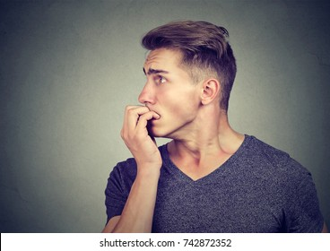 Preoccupied anxious man biting his fingernails looking to the side