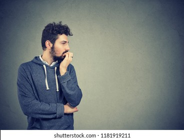 Preoccupied anxious young man biting his fingernails