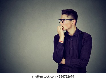 Preoccupied anxious young man biting his fingernails looking sideway at blank copy space