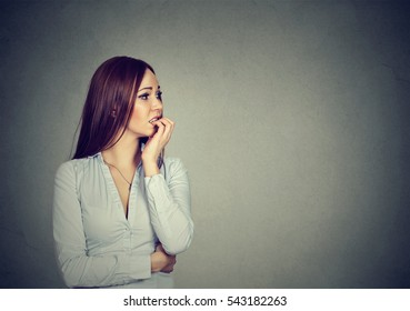 Preoccupied anxious young woman biting her fingernails