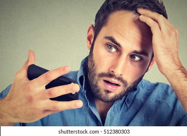 Preoccupied shocked man feeling head, surprised he is losing hair, receding hairline, bad news isolated on gray background. Negative facial expressions, emotion