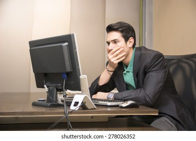 Preoccupied, worried, desperate young male worker staring at computer screen in his office