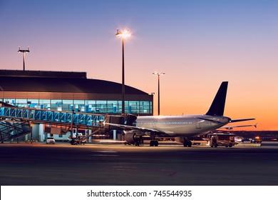 Vorbereitung des Flugzeugs vor dem Flug. Flughafen bei buntem Sonnenuntergang.