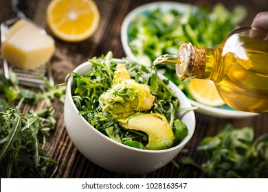 Preparation of avocados in green salad. Vegetables and a bottle of olive oil.