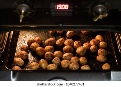 Preparation of baked potatoes in the oven. A woman's hand takes potatoes from the oven out of the oven