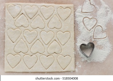 Preparation of the biscuits for Valentine's Day. Dough, flour and cookie cutters on the table