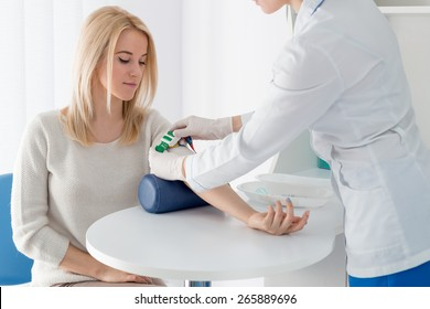 Preparation for blood test with beautiful young blond woman by female doctor in white coat medical uniform on the table in white bright room. Nurse patient hand grips green jute.