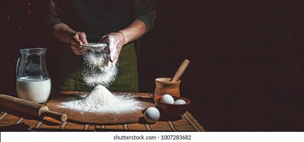 Preparation of bread dough. Bakery, baker's hands, flour is poured, flying flour