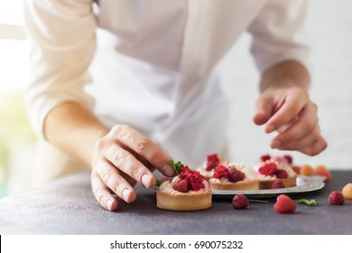 Preparation of cakes with raspberries on a table