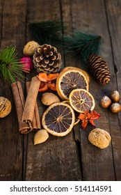 Preparation for the Christmas with lots of Xmas Symbols such as nuts, orange slices, tree branches, cranberries, cinnamon sticks, cones on Wooden Rustic Background