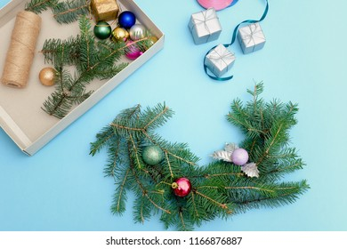 Preparation for Christmas wreath. Spruce branch, ornaments.  Blue background.