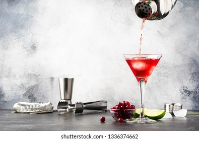 Preparation Classic alcoholic cocktail cosmopolitan with vodka, liqueur, cranberry juice, lime, ice and orange zest, gray bar counter background, place for text