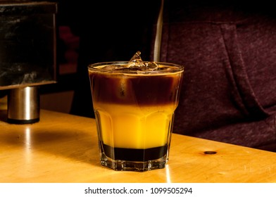 Preparation of a colorful cocktail of bumble or crazy bee with orange juice caramel syrup and espresso coffee in a glass cup on a wooden table coffee maker on the background