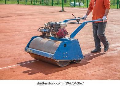 Preparation and construction of a clay tennis court. Compaction of the soil with a vibratory roller.